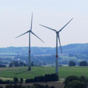 Das Icon zeigt zwei der vier Windenergieanlagen bei Hagedorn. Im Hintergrund sind Ausläufer des bergigen Teutoburgerwaldes zu sehen.