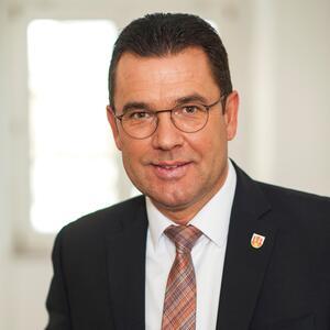 Das Foto zeigt ein Portrait des Bürgermeisters Carsten Torke im grauen Sakko und weißem Hemd mit rot weiß blau quer gestreifter Krawatte.